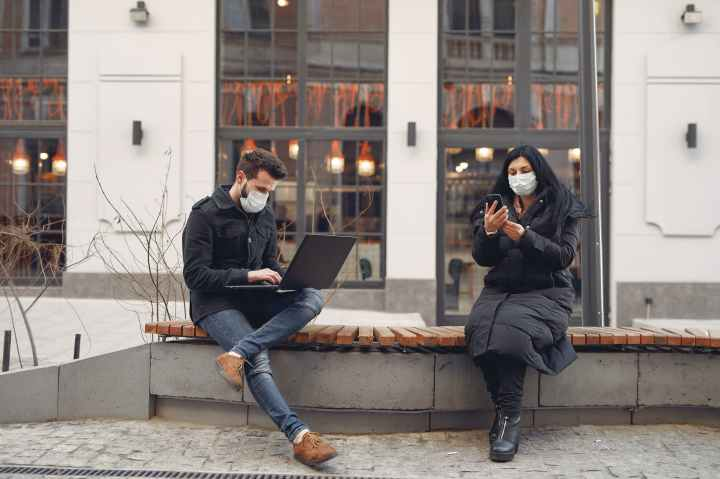 young couple wearing medical masks with laptop and smartphone on city street